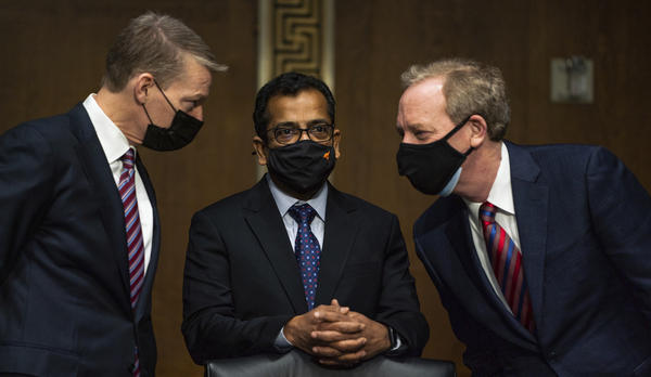 Three tech executives confer before testifying before the Senate Intelligence Committee in February about an attack on U.S. government computers blamed on Russia. They are FireEye CEO Kevin Mandia (left), SolarWinds CEO Sudhakar Ramakrishna (center) and Microsoft President Brad Smith. In the wake of multiple hacks, the Biden administration is searching for ways to stop them.