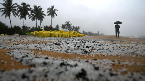 A man walks past sacks containing debris washed ashore from the X-Press Pearl on a beach in Colombo on Thursday. The plastic pellets will break down and be more difficult to clean up over time, marine biologist Asha de Vos says.