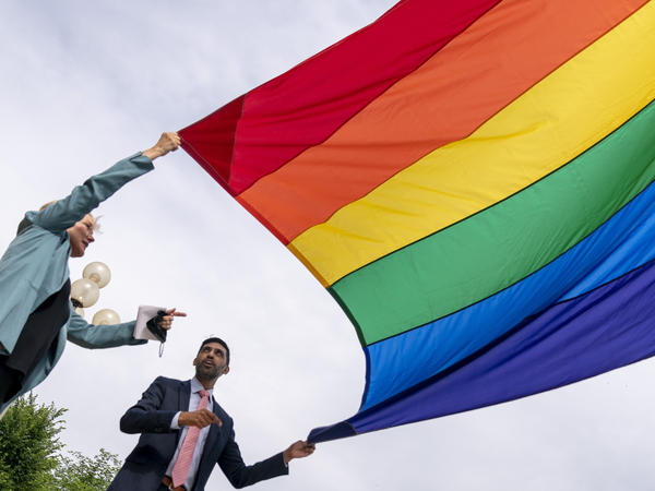 Energy Secretary Jennifer Granholm and Department of Energy Chief of Staff Tarak Shah help raise the Progress Pride Flag outside the DOE in Washington on Wednesday. The Pentagon decided not to allow the flag to fly on military installations for Pride Month.