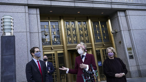 E. Jean Carroll (center), who says former President Donald Trump raped her in the 1990s, speaks to reporters as she leaves the courthouse in New York following an October hearing in her defamation lawsuit. The Justice Department said Tuesday it will continue its defense of Trump.