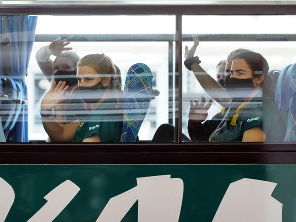 Australian softball players, the first foreign team to arrive for the Tokyo Olympic Games, wave from their bus after arriving at Narita International Airport on June 1.
