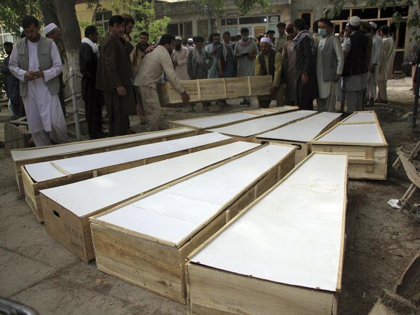 The coffins of the victims in Tuesday's attack are placed on the ground at a hospital in northern Baghlan province, Afghanistan, on Wednesday. Workers of the HALO Trust demining organization were attacked on Tuesday night by armed gunmen.