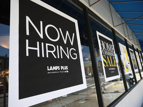 """A pedestrian walks by a """"Now Hiring"""" sign outside of a Lamps Plus store in San Francisco on on June 3. Four states, including Mississippi, are moving to end an extra $300-a-week unemployment benefit, arguing the pay is discouraging people from finding work."""
