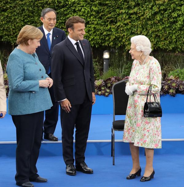 """Queen Elizabeth II with Germany's Angela Merkel, Japan's Yoshihide Suga and France's Emmanuel Macron at a reception Friday. The British monarch joined the G-7 leaders for dinner. """"Are you supposed to be looking as if you're enjoying this?"""" she asked as the cameras clicked for a traditional group photo."""
