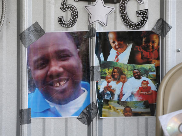 In this July 6, 2016 file photo, photos of Alton Sterling are taped to a makeshift memorial outside the Triple S convenience store in Baton Rouge, La. Sterling, was shot and killed outside the store by Baton Rouge police.