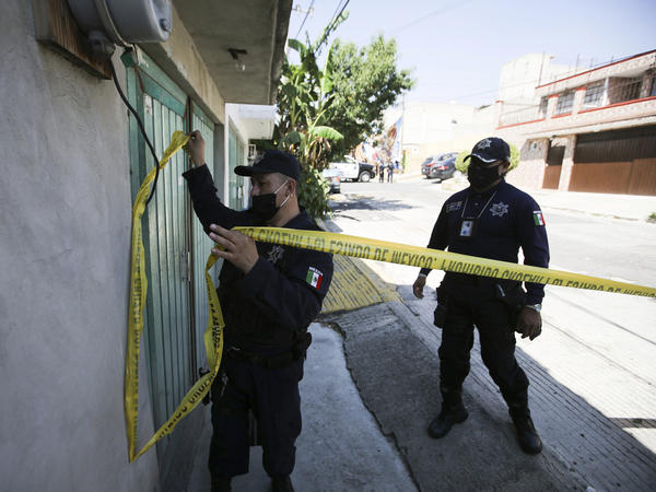 Police mark a security perimeter around the house where bones were found under the floor in the Atizapan municipality of the State of Mexico, on May 20, 2021. Police have turned up bones and other evidence under the floor of the house where a man was arrested for allegedly stabbing a woman to death and hacking up her body.