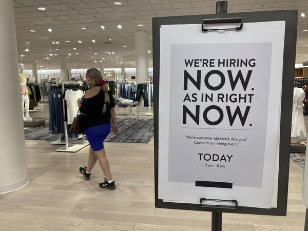 A customer walks behind a sign at a Nordstrom in Coral Gables, Fla., store seeking employees in May.