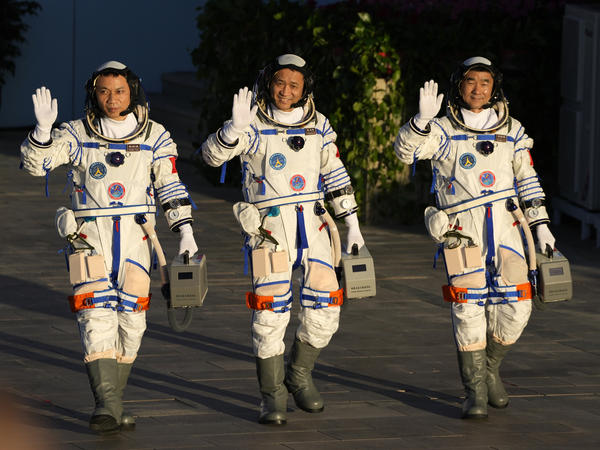 Chinese astronauts, from left, Tang Hongbo, Nie Haisheng, and Liu Boming wave as they prepare to board for liftoff Thursday at the Jiuquan Satellite Launch Center in Jiuquan in northwestern China. China plans to launch three astronauts onboard the Shenzhou-12 spaceship who will be the first crew members to live on China's new orbiting space station Tianhe, or Heavenly Harmony.