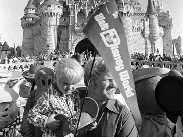 When Disney World opened on Oct. 1, 1971, tickets for adults were just $3.50. Here, William Windsor Jr. carries his son Lee, past Cinderella's castle on opening day.