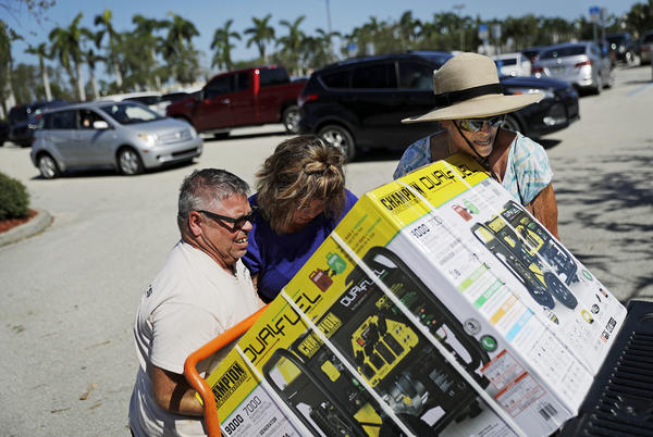 Don Jordan, from left, Lisa Jordan and Pat Lamke struggle to load a generator they just bought at a Costco store as it opened for the first time since Hurricane Irma passed through in Miromar Lakes, Fla., Wednesday, Sept. 13, 2017. (AP Photo/David Goldman)