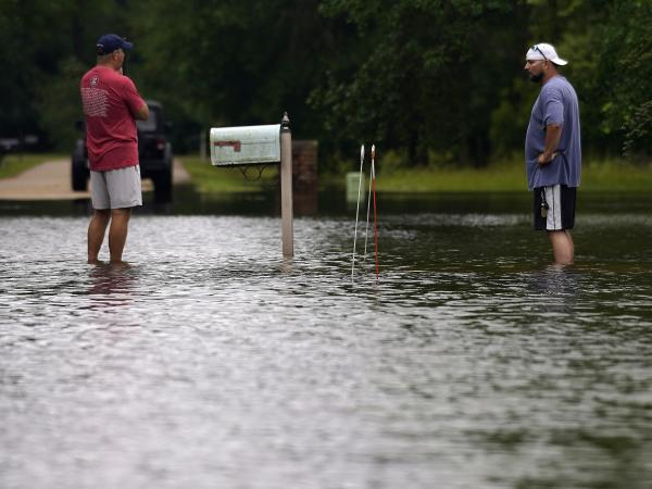 Danny Gonzales (right) stands in front of his flooded house with his neighbor Bob Neal after Tropical Storm Claudette passed through, in Slidell, La., on Saturday.