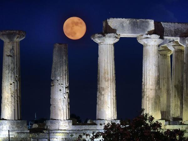 June's full moon, known as the strawberry moon, was named for its appearance during the strawberry picking season. Here, the strawberry moon rises above the Apollo Temple in ancient Corinth, on June 17, 2019.