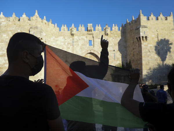 Demonstrators wave the Palestinian flag during a protest in Damascus Gate, just outside Jerusalem's Old City on June 19. Palestinians and Jewish settlers hurled stones, chairs and fireworks at each other in a tense Jerusalem neighborhood, where settler groups are trying to evict several Palestinian families, officials said Tuesday.