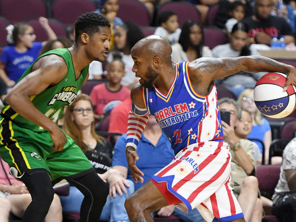 """Carlos """"Dizzy"""" English of the Harlem Globetrotters drives against Shaquille Burrell of the Washington Generals during their exhibition game at the Orleans Arena near Las Vegas."""