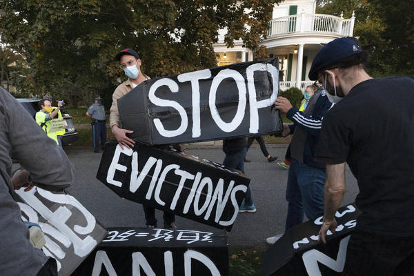 Housing activists erect a sign in front of Massachusetts Gov. Charlie Baker's house in Swampscott, Mass., on Oct. 14, 2020. The Centers for Disease Control and Prevention has extended a moratorium on evictions until the end of July.