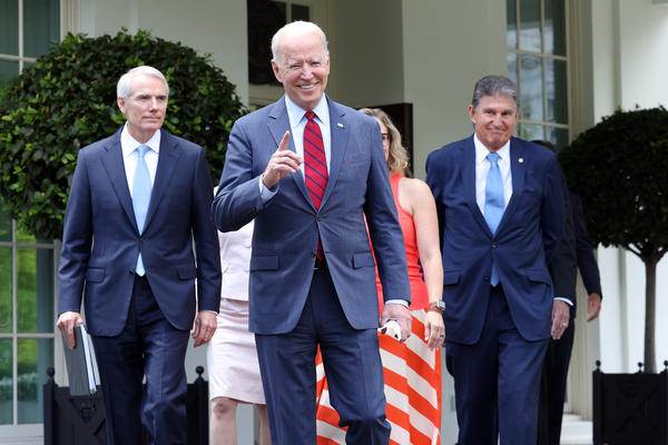 President Biden, joined by a group of senators, gets ready to deliver remarks Thursday at the White House after reaching a bipartisan deal on an infrastructure package.