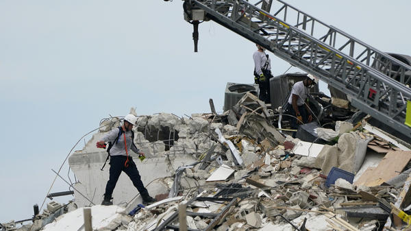 Rescue workers walk atop the rubble of a 12-story beachfront condo building that partially collapsed in Florida's Miami-Dade County.