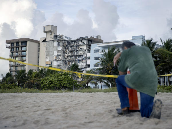 A man prays Friday near where search and rescue operations are ongoing at the partially collapsed 12-story Champlain Towers South condo building in Surfside, Fla.