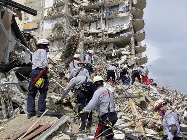 Search and rescue workers search for survivors among the Champlain Towers South Condo rubble in Surfside, Fla. The building partially collapsed Thursday, leaving at least four people dead and another 159 missing.