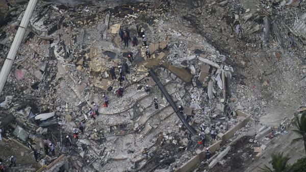 Search and rescue crews work among the rubble at the Champlain Towers South in Surfside, Fla. Rescuers are combating fire, smoke and a complex debris field as they search for survivors.