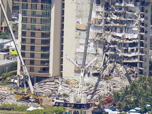 Crews work near a open tunnel, center near the bottom, in the rubble at the Champlain Towers South Condo on Sunday in Surfside, Fla. More than 150 people were still unaccounted for two days after Thursday's collapse.