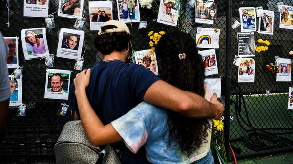 People visit a makeshift memorial for the victims of the building collapse, near the site of the accident in Surfside, Fla., on Sunday.
