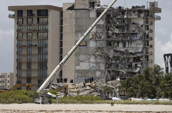 Members of the South Florida Urban Search and Rescue Team look for survivors in the partially collapsed 12-story Champlain Towers South condo building in Surfside, Fla.