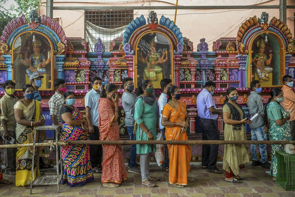 On June 25, people queued up to register for a COVID-19 vaccine at a site outside a Hindu temple in Hyderabad. Vaccinations are now being administered after a series of missteps led to a shortage of doses. If all goes well, India's public health agency hopes to be vaccinating up to 10 million people a day by late July.