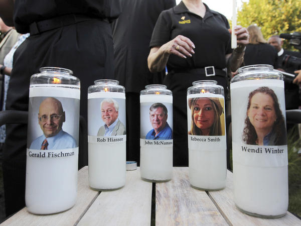 In this June 29, 2018, file photo, pictures of five employees of the <em>Capital Gazette</em> newspaper adorn candles during a vigil across the street from where they were slain in the newsroom in Annapolis, Md.
