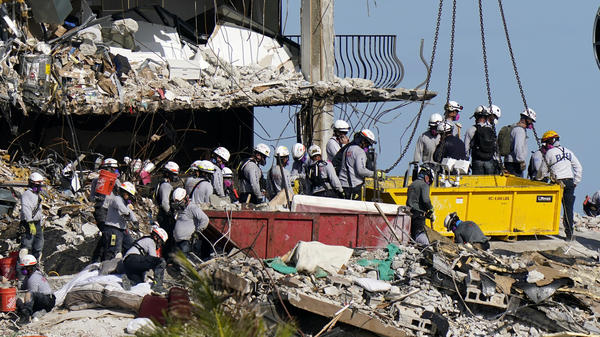 Workers search the rubble  Monday at the Champlain Towers South condo collapse in Surfside, Fla. President Biden plans to visit the site on Thursday.