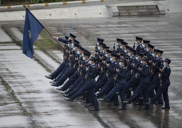Hong Kong police show their new goose step marching style on National Security Education Day at a police school in Hong Kong on April 15.
