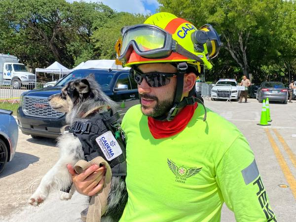 Moises Soffer, a volunteer member of Cadena International's search-and-rescue team working at the site of the condo building collapse, holds a trained search dog named Oreo in Surfside, Fla., on Sunday.