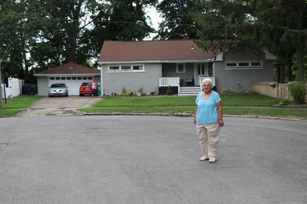 Luella Kenny standing in front of the house she left behind almost 40 years ago