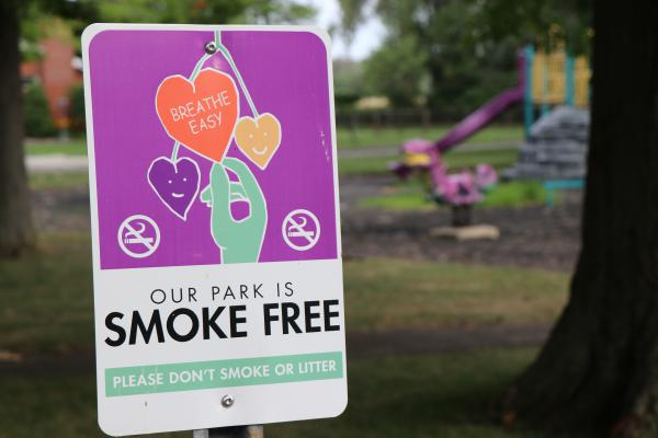 A smoke free sign right outside a children's playground that's located next to a fenced off area at Love Canal