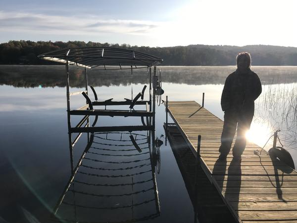 Cherie Hogan stands on the dock in front of her home on Six Mile Lake, which had its first ever harmful algal bloom this year.