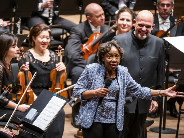 """Tania León speaks at the premiere of her piece """"Stride,"""" one of 19 pieces composed by women that the New York Philharmonic commissioned to celebrate the 100th anniversary of the 19th Amendment."""