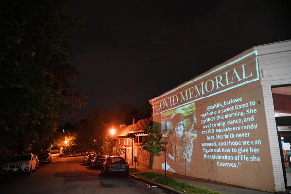 """Video artist Robin Bell projected the words """"Covid Memorial,"""" onto the brick wall of a Subway sandwich shop in Washington, D.C. Below them scrolled a slideshow of faces of COVID-19 victims, along with messages their loved ones had posted on social media."""
