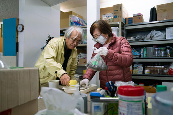 """Takenori Kobayashi (left) and his wife Tomoko Kobayashi bring soil samples into what they refer to as a """"grandma and grandpa lab"""" to test it for radiation, in Fukushima prefecture, Japan."""