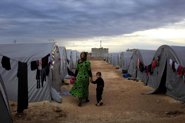 A Kurdish refugee mother and son from the Syrian town of Kobani walk beside their tent in a camp in the Turkish town of Suruc on the Turkish-Syrian border in 2014. President-elect Joe Biden aims to reverse the Trump administration's dramatic cuts to refugee admissions.