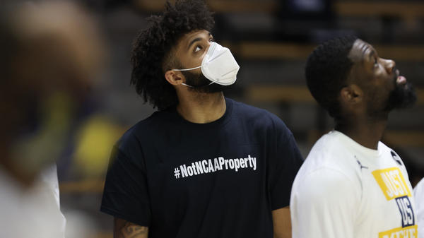 """Wearing a shirt that says, """"#NotNCAAProperty,"""" injured University of Michigan basketball player Isaiah Livers looks on prior to his team's NCAA tournament game against Texas Southern on March 20. On Wednesday the U.S. Supreme Court hears a case testing the NCAA's limits on compensation for student athletes."""