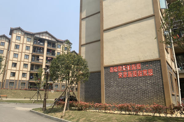 """Apartments in Qixingguan, a new district in Bijie, China, were built for the residents of poor, remote villages. A patriotic slogan on one building says: """"Resettlement to a new home. Thank the Communist Party for a happy, peaceful new home."""""""