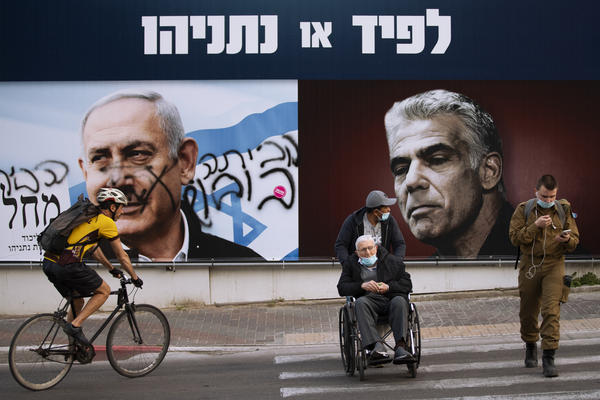 """An election campaign billboard for the Likud party shows its leader, Prime Minister Benjamin Netanyahu (left), and opposition party leader Yair Lapid, in Ramat Gan, Israel, days before that country's election in March. The banner reads """"Lapid or Netanyahu."""" Spray paint on Netanyahu's portrait reads, """"Go home."""""""