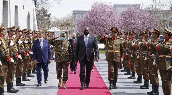 """U.S. Defense Secretary Lloyd Austin (center) reviews an honor guard at Afghanistan's presidential palace in Kabul on March 21. President Biden says all U.S. troops will leave Afghanistan by September, though the Americans will still assist from """"over the horizon."""""""
