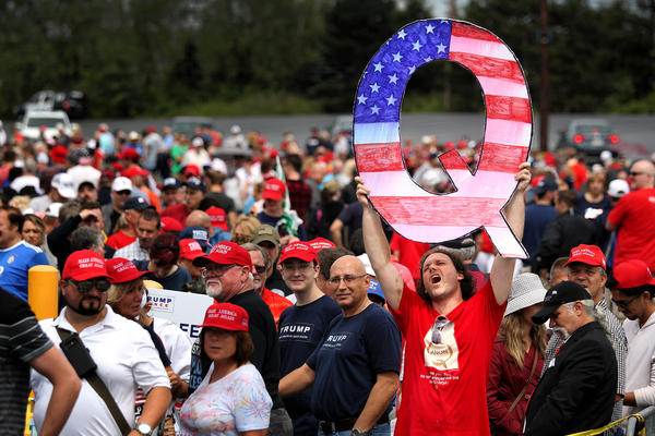 """David Reinert holds up a large """"Q"""" sign that represents QAnon while waiting in line to see then-President Donald Trump at his rally in Wilkes-Barre, Pa., on Aug. 2, 2018."""