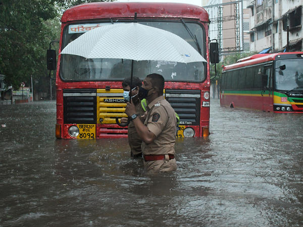 A police officer helps a public transport driver cross a flooded street caused by heavy rain from Cyclone Tauktae in Mumbai.
