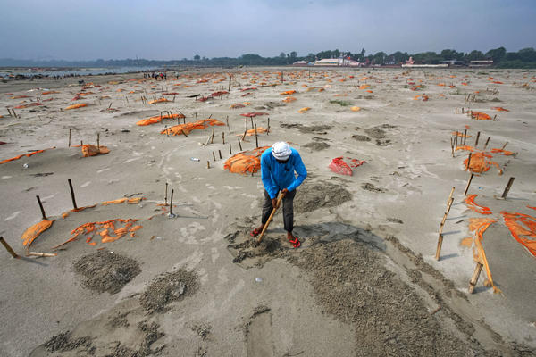 Rains have washed away the top layer of sand of shallow graves at a cremation ground on the banks of the Ganges River in Shringverpur, northwest of Allahabad, Uttar Pradesh, India. Coronavirus testing is limited in parts of rural India, but some of the people buried there are believed to have died of COVID-19.