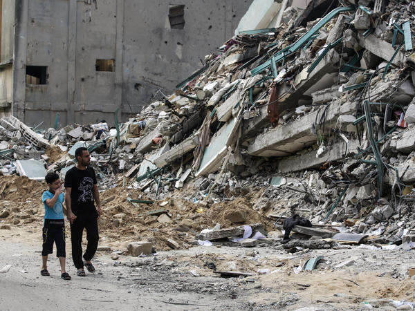 Palestinians walk past a destroyed tower after 11 days of deadly fighting that pounded Gaza and forced countless Israelis to seek shelter from rockets.