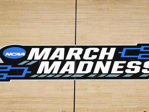 The March Madness logo is seen during a men's college basketball NCAA tournament game in Indianapolis. The Supreme Court has eroded<strong> </strong>the difference between elite college athletes and professional sports stars.