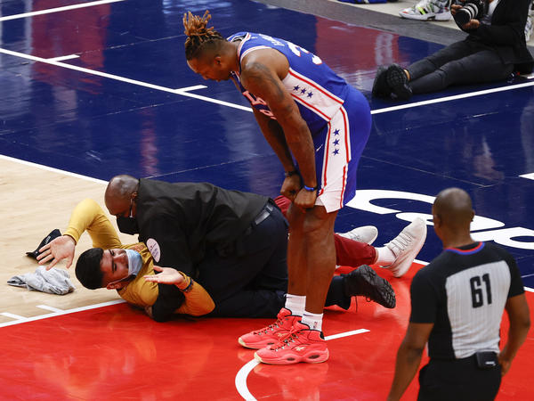 Dwight Howard of the Philadelphia 76ers looks down at a fan who ran onto the court and was tackled by security in Game 4 of the Eastern Conference first-round series against the Washington Wizards on Monday.