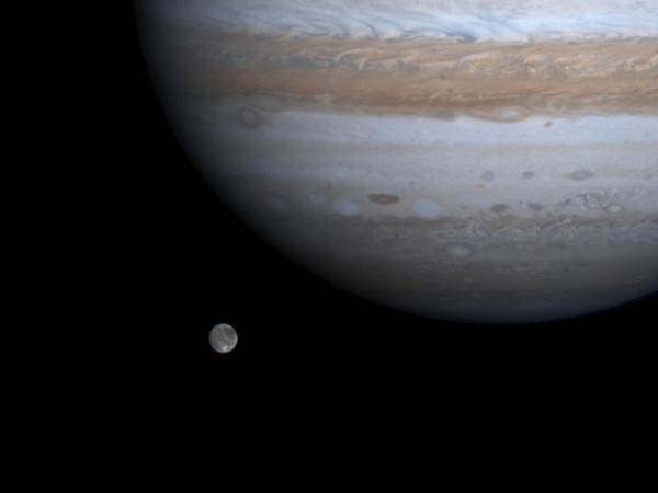 The solar system's largest moon, Ganymede, is pictured with Jupiter in a photo by NASA's Cassini spacecraft on Dec. 3, 2000. NASA's Juno mission got close to Ganymede on Monday.